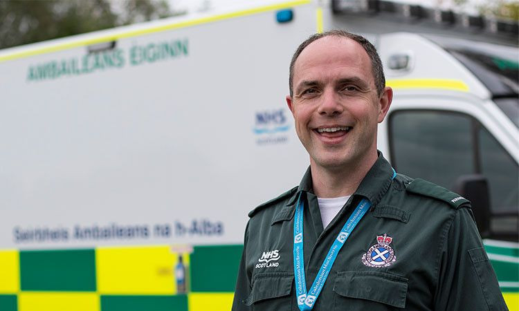 Allan MacFadyen in his green paramedic uniform, standing in front of an ambulance.