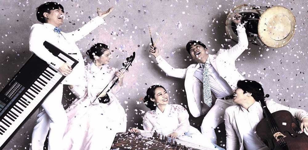 A group of musicians dressed in white, standing in various poses with white confetti falling around them.