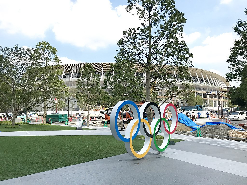 Olympic rings in front of a partially built Olympic stadium in Tokyo, Japan. Built by Kengo Kuma.