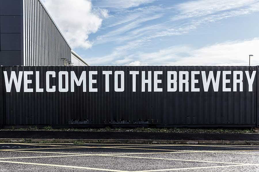 A wall with the words Welcome to the Brewery written across it in white text.