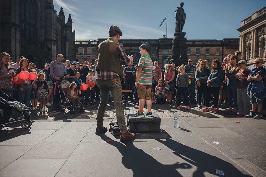 A street performer and a young boy standing on a brown suitcase on the Royal Mile, at the Edinburgh Festival.