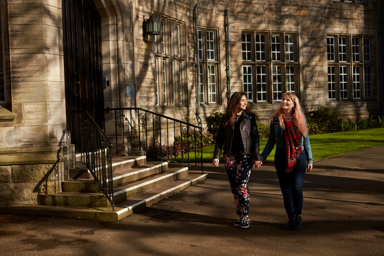 Two students walking in the grounds of the University of St Andrews