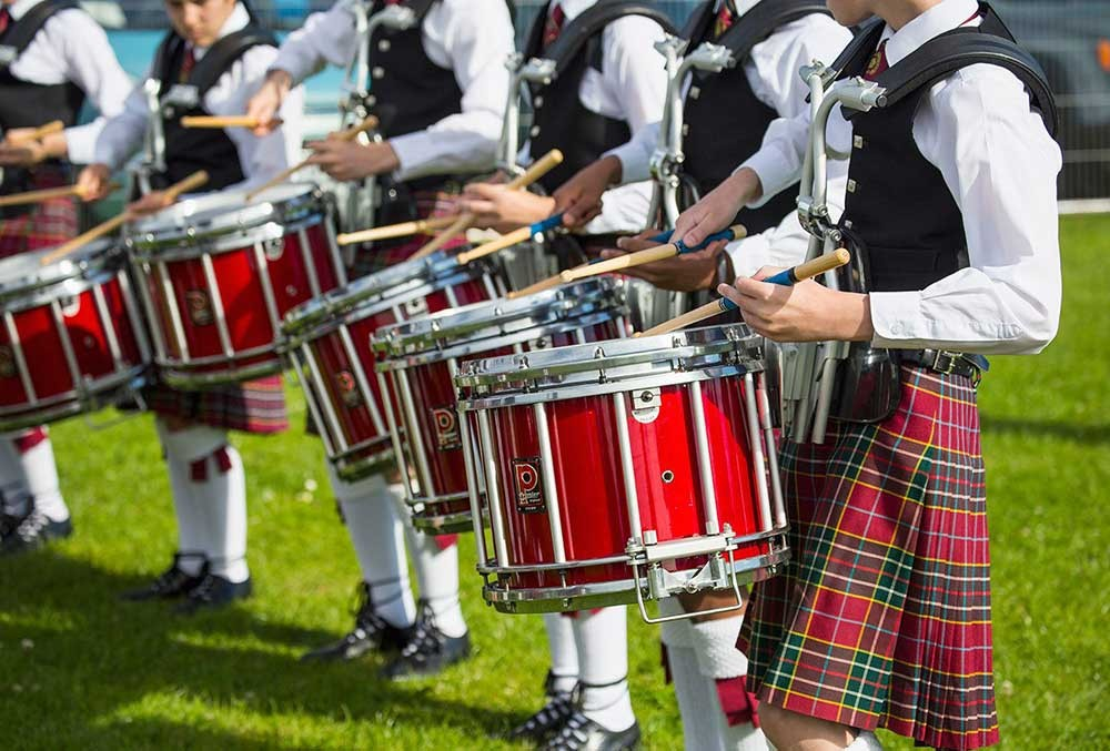 A line of Scottish drummers playing in kilts and waist coats outside.