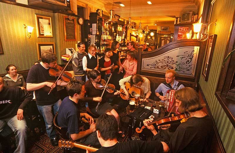 Musicians playing instruments such as guitars, violins and an accordion in a traditional Scottish pub.