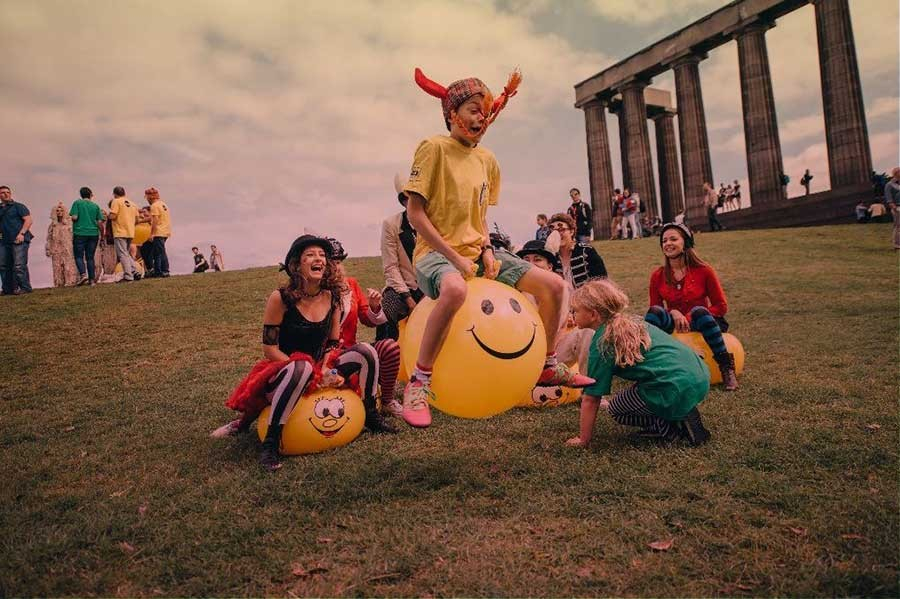 A group of children play on yellow space hoppers.
