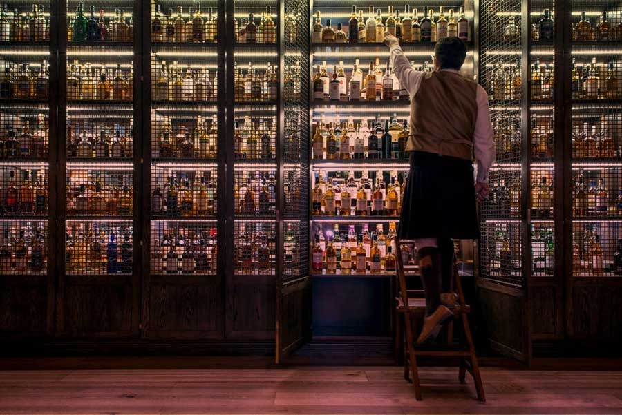 A man in a kilt gets a whisky bottle from a large whisky shelf.