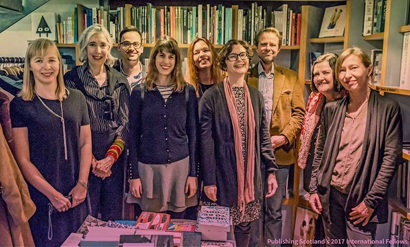 A group of men and women standing in a gallery book shop.