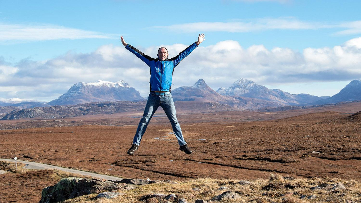 Allan MacFadyen jumping up in front of a mountainous landscape.