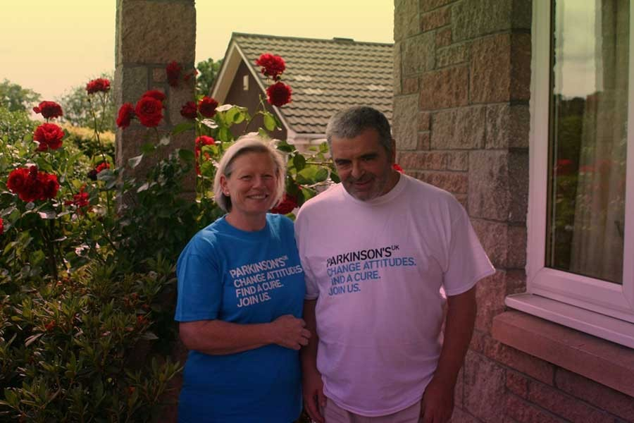 A man and a woman standing next to each other, wearing Parkinsons UK tshirts.