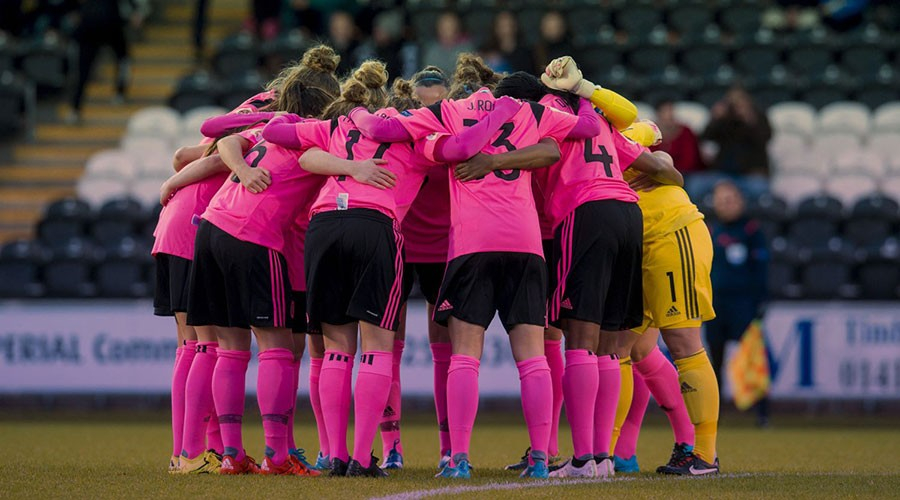 A group of female footballers in a pink and black strip, standing in a huddle.
