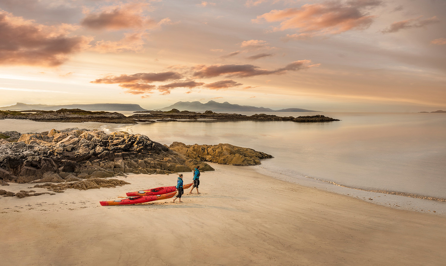 Kayakers head to the sea with their kayaks on Cambusdarach beach,